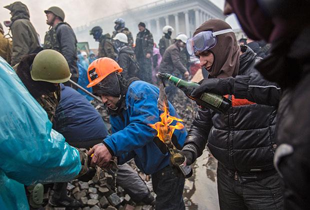 Сторонники оппозиции поджигают бутылки с зажигательной смесью на Майдане Независимости в Киеве, где начались столкновения митингующих и сотрудников милиции.