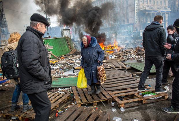 Пожилая женщина и сторонники оппозиции на Майдане Независимости в Киеве, где начались столкновения митингующих и сотрудников милиции.