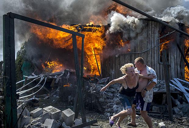 Местные жители спасаются от пожара, возникшего в результате авиационного удара вооруженных сил Украины по станице Луганская.