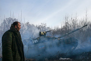 A man stands next to a pro-Russian separatist's tank riding near the village of Rozsypne (Rassypnoye), eastern Ukraine, December 15, 2014