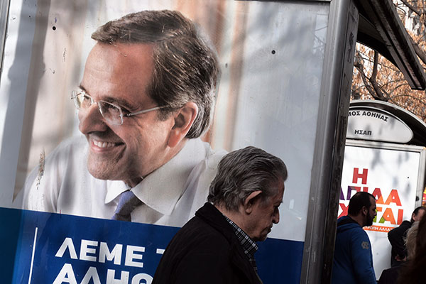 People stand near campaign posters of Greek prime minister Antonis Samaras (L), of the conservative New Democracy party, and leftist Syriza party (R) on January 22, 2015, ahead of Greece's general election on January 25.  Greeks vote on January 25 in a general election for the second time in three years, with radical leftists Syriza leading the polls with a promise to renegotiate the international bailout that has imposed five years of austerity on the country. AFP PHOTO/ LOUISA GOULIAMAKI