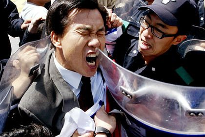 Полиция задерживает протестующего перед японским культурным центром в Сеуле. 22 апреля 2005