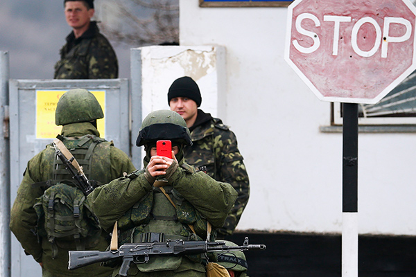 Armed men, believed to be Russian servicemen, stand guard outside an Ukrainian military base in the village of Perevalnoye near the Crimean city of Simferopol March 9, 2014. Shots were fired in Crimea to warn off an unarmed international team of monitors and at a Ukrainian observation plane, as the standoff between occupying Russian forces and besieged Ukrainian troops intensified. REUTERS/Thomas Peter