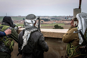 Fighters of the Kurdish People's Protection Units (YPG) carry their weapons and use a pair of binoculars in the outskirts of Tal Tamr town as they monitor the movements of Islamic State fighters who recently captured several villages February 25, 2015. Kurdish militia pressed an offensive against Islamic State in northeast Syria on Wednesday, cutting one of its supply lines from Iraq, as fears mounted for dozens of Christians abducted by the hardline group. The Assyrian Christians were taken from villages near the town of Tel Tamr, some 20 km (12 miles) to the northwest of the city of Hasaka. There has been no word on their fate. There have been conflicting reports on where the Christians had been taken. REUTERS/Rodi Said