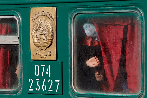 Migrant workers are seen through a carriage window as they wait for departure of a train bound for Tajikistan in Moscow, October 7, 2011.