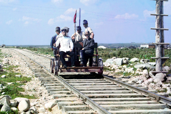 an official and four railway workers(?)riding on a railroad handcar.