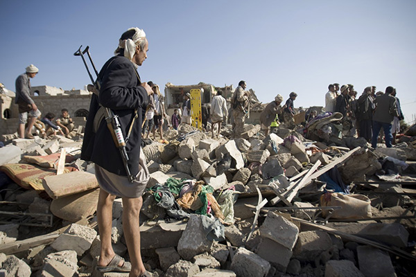 A Houthi Shiite fighter stand guard as people search for survivors under the rubble of houses destroyed by Saudi airstrikes near Sanaa Airport, Yemen,