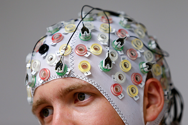 Test person Niklas Thiel poses with an electroencephalography (EEG) cap which measures brain activity, at the Technische Universitaet Muenchen (TUM) in Garching near Munich September 9, 2014. The researchers from TUM and the Technische Universitaet Berlin (team Phypa) try to find ways to control an airplane with computer translated brain impulses without the pilot touching the plane's controls. The solution, if achieved, would contribute to greater flight safety and reduce pilots' workload. Picture taken September 9, 2014.    REUTERS/Michaela Rehle (GERMANY - Tags: HEADSHOT SOCIETY SCIENCE TECHNOLOGY) - RTR45SGY