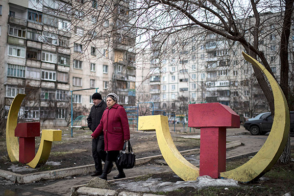 Local residents walk past Soviet-era  hammer and sickle sculptures outside an apartment building damaged after Saturday's shellingin Mariupol, Ukraine, Wednesday, Jan. 28, 2015. The military conflict between Russia-backed separatists and the government forces in eastern Ukraine has been raging since April, claiming more than 5,100 lives, according to the United Nations. (AP Photo/Evgeniy Maloletka)