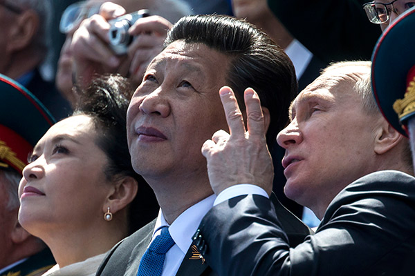 Russian President Vladimir Putin, right, gestures while speaking with Chinese President Xi Jinping, second left, watching the Victory Parade marking the 70th anniversary of the surrender of Nazi Germany in World War II, in Red Square, Moscow, Russia, Saturday, May 9, 2015. Xi's wife Peng Liyuan is at left. (AP Photo/Alexander Zemlianichenko, Pool)
