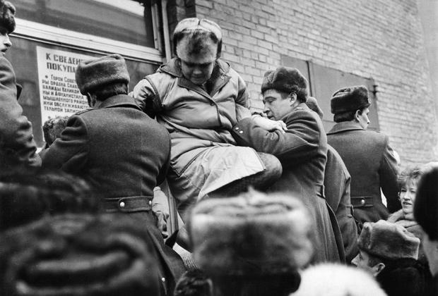 Сотрудники милиции вытаскивают на руках женщину из очереди у входа в магазин, начало 1990-х
