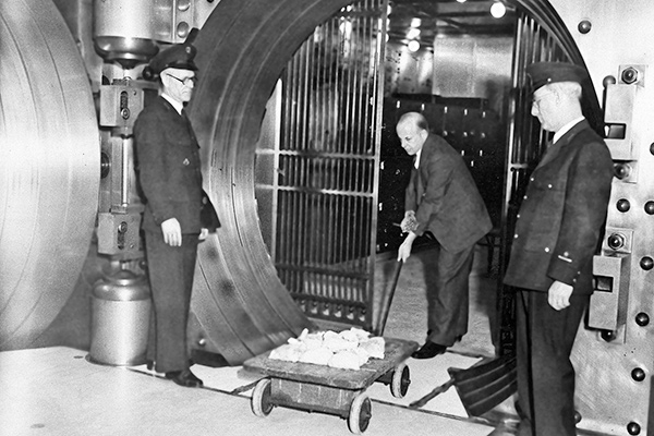 "Officials of the Empire Trust Company believe the largest single deposit made by an individual since the government suspended gold payments was made by a person who brought in $35,000 in gold in New York on March 8, 1933. Officials of the bank do not know the depositior's motive in bringing his gold out of hiding but assume it was a case of ""Conscience."" The deposit in little bags is shown being taken to the vaults, escorted by an armed guard.(AP Photo)"
