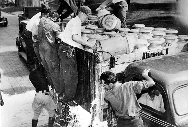 Забастовка фермеров во время Великой депрессии. Фермеры выливают молоко на тротуар.