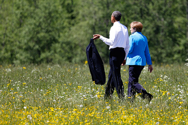 German Chancellor Angela Merkel, right, walks with U.S. President Barack Obama after a group photo at the G-7 summit at Schloss Elmau hotel near Garmisch-Partenkirchen, southern Germany, Sunday, June 7, 2015. The two-day summit will address such issues as climate change, poverty and the situation in Ukraine. (AP Photo/Markus Schreiber)