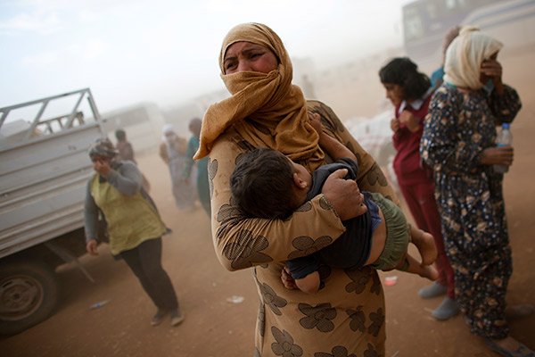 A Kurdish Syrian refugee waits for transport during a sand storm on the Turkish-Syrian border near the southeastern town of Suruc in Sanliurfa province, September 24, 2014. The United Nations refugee agency said on Tuesday it was making contingency plans in case all 400,000 inhabitants of the Syrian Kurdish town of Kobani fled into Turkey to escape advancing Islamic State militants.           REUTERS/Murad Sezer (TURKEY  - Tags: POLITICS TPX IMAGES OF THE DAY CIVIL UNREST CONFLICT)   - RTR47JGB