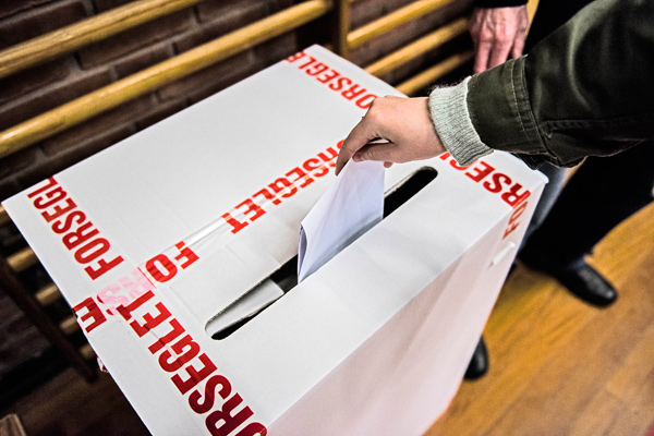 "A voter casts a ballot in the voting box wrapped by tapes bearing letters that read: ""Sealed"" at a primary school in Copenhagen, Denmark, Thursday morning June 18, 2015."