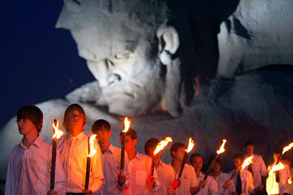 Belarusian school boys hold torches as they stand in front of one of the most important Soviet WWII war monuments marking the heroic resistance of the Red Army against the surprise German attack during a ceremony marking the 70th anniversary of Nazi invasion in the town of Brest, 360 kilometers (223 miles) southwest of Minsk, Belarus, early Wednesday, June 22, 2011. When Nazi Germany invaded the Soviet Union on June 22, 1941, the Brest Fortress defenders contained Nazi troops for a month. (AP Photo/Sergei Grits)