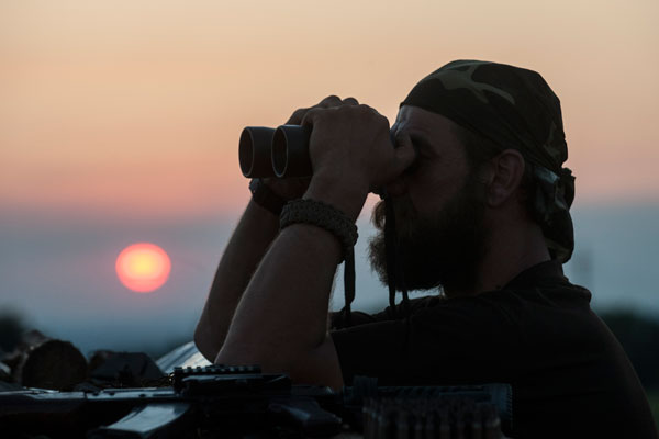 In this photo taken Monday, June 22, 2015, a Ukrainian serviceman from the Kiev-2 volunteer battalion uses binoculars at the frontline in the village of Krymske, east Ukraine.  Few places along the front line in east Ukraine see regular fighting as bitter as the village of Krymske. For now, Krymske is in the hands of Ukrainian government forces and the volunteer battalions that fight alongside them. (AP Photo/Evgeniy Maloletka)