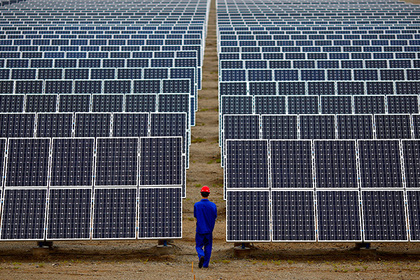 A worker inspects solar panels at a solar Dunhuang, 950km (590 miles) northwest of Lanzhou, Gansu Province September 16, 2013. China is pumping investment into wind power, which is more cost-competitive than solar energy and partly able to compete with coal and gas. China is the world's biggest producer of CO2 emissions, but is also the world's leading generator of renewable electricity. Environmental issues will be under the spotlight during a working group of the Intergovernmental Panel on Climate Change, which will meet in Stockholm from September 23-26. REUTERS/Carlos Barria (CHINA - Tags: ENERGY BUSINESS ENVIRONMENT) - RTX13UEF