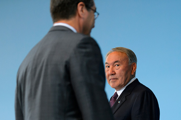 Kazakhstan's President Nursultan Nazarbayev (R) looks at WTO Director general Roberto Azevedo during the accession ceremony at the World Trade Organization (WTO) headquarters in Geneva, Switzerland July 27, 2015. Kazakhstan is the 162nd member of the organization. REUTERS/Fabrice Coffrini/Pool - RTX1M0D6