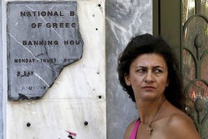 A Greek woman pauses by a broken marble National Bank sign outside a branch in Athens July 8, 2015. Euro zone members have given Greece until the end of the week to come up with a proposal for sweeping reforms in return for loans that will keep the country from crashing out of Europe's currency bloc and into economic ruin. REUTERS/Yannis Behrakis      TPX IMAGES OF THE DAY      - RTX1JJ7V