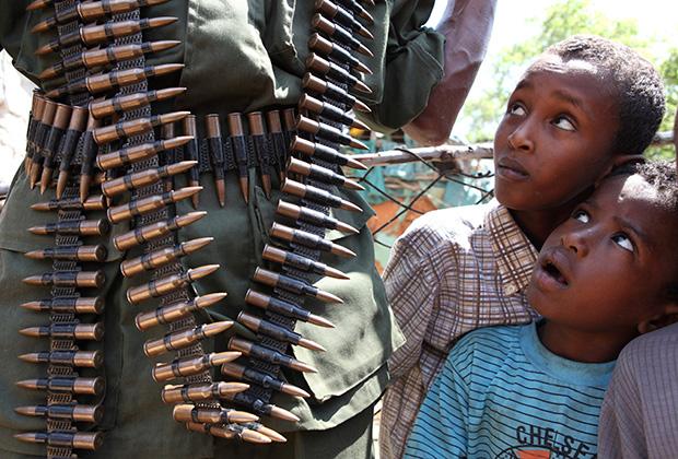 Сомалийские дети смотрят на солдата Переходного правительства