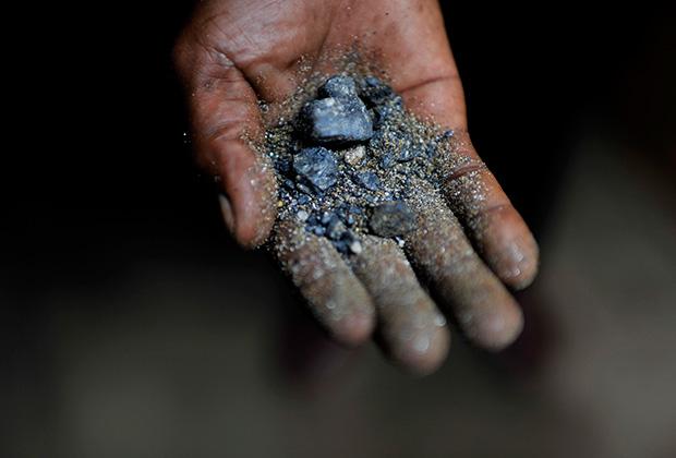 Шахтер из Демократической Республики Конго держит в руке минерал колтан