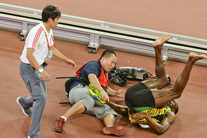 Usain Bolt of Jamaica (R) falls after being hit by a cameraman (C) on a Segway as he celebrates after winning the men's 200 metres final during the 15th IAAF World Championships at the National Stadium in Beijing, China, August 27, 2015. REUTERS/Stringer CHINA OUT. NO COMMERCIAL OR EDITORIAL SALES IN CHINA - RTX1PXER