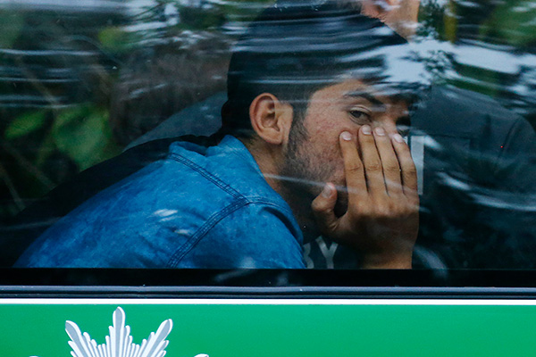 A migrant sits in a police bus after coming from Austria to Germany at the highway A3 in Pocking near Passau, Germany,  Tuesday, Sept. 1, 2015. Hundreds of migrants are arriving every day, after making perilous journeys through Europe. (AP Photo/Matthias Schrader)