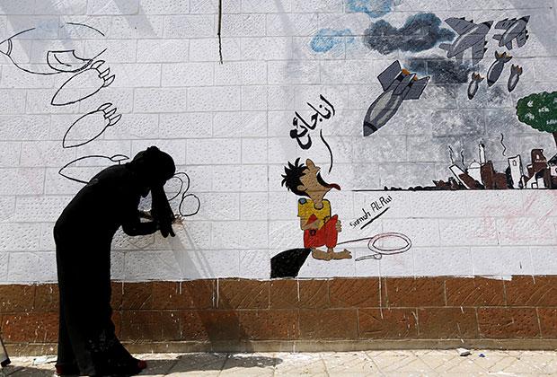 Сторонники хоуситов рисуют граффити на стене посольства Саудовской Аравии в Сане