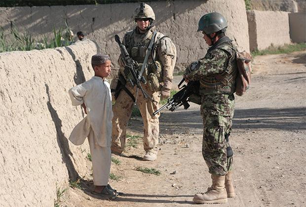 Солдаты говорят с афганским мальчиком, пока их сослуживцы за кадром допрашивают его спутника