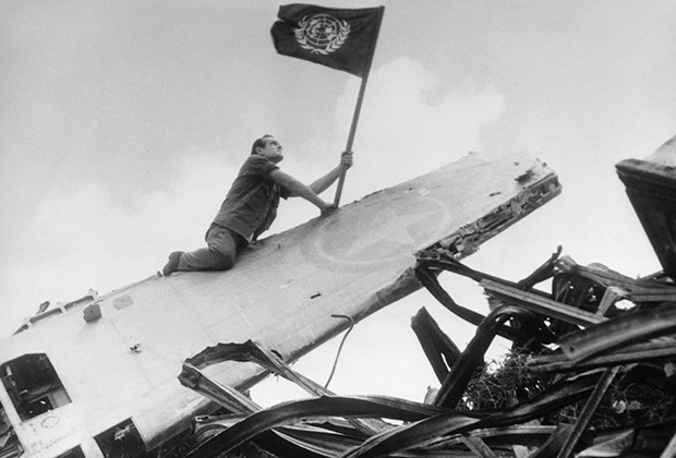 Американский солдат водружает флаг ООН на крыло сбитого «Яка», 1951 год