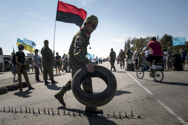 A member of a right sector nationalist group carries tires to block a road heading towards Crimea, in the village of Chongar, Ukraine, on Sunday, Sept. 20, 2015. The radical Right Sector group and Pro-Kiev Crimean tartars leadership organized improvised checkpoints on all three roads connecting the Ukrainian mainland and Russian-annexed Crimean peninsula, aiming to prevent trucks carrying goods to cross Russia-Ukraine border. (AP Photo/Evgeniy Maloletka)