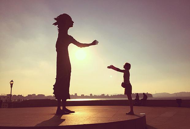 """Статуя """"Мать иммигранта"""" и иммигрантка из России на пляже Сан-Лоренсо в Хихоне, Астурия"""