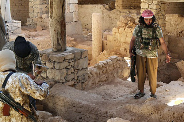 This picture released late Thursday, Aug. 20, 2015, by an Islamic State militant-affiliated website, shows Islamic State Milittants standing inside the ancient monastery of the Saint Eliane, near the town of Qaryatain which IS captured in early August, in Homs province, Syria. A priest and activists say the Islamic State group has demolished an ancient monastery in central Syria. A Christian clergyman told The Associated Press in Damascus that IS militants also wrecked a church inside the monastery that dates back to the first Christian centuries. The priest, who spoke Friday on condition of anonymity for fear of reprisals, said the monastery included an Assyrian Catholic church. (Islamic State militant website via AP)