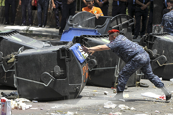 A policeman removes a barricade built with garbage bins by protesters against a hike in electricity prices in Yerevan, Armenia, July 6, 2015. Police forces pushed protesters from the main avenue after a standoff lasting two weeks, local media reported. REUTERS/Hayk Baghdasaryan/Photolure