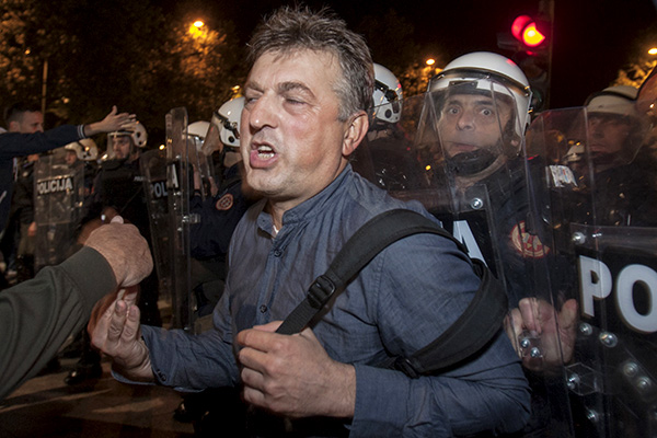 Riot policemen push demonstrators while attempting to disperse them outside the parliament building in the capital Podgorica, Montenegro, October 17, 2015. Montenegro's police used teargas on Saturday to disperse hundreds of anti-government protesters outside the parliament building in the capital Podgorica and local media said several people had suffered light injuries. The ex-Yugoslav republic's main opposition bloc, the Democratic Front, set up tents in front of the parliament 20 days ago demanding the resignation of veteran Prime Minister Milo Djukanovic and the formation of an interim government pending fresh elections.