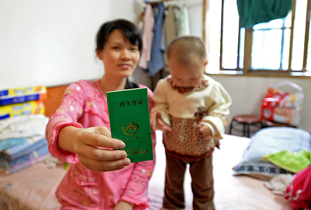 Женщина демонстрирует сертификат, дающий право на второго ребенка