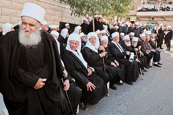 Majdal Shams, Israel - Druze residents of Majdal Shams in the Golan Heights march in the village's main square waving Druze and Syrian flags in support of Assad's Syrian regime and in solidarity with their Druze brethren in Syria. ISIS and other rebel forces are reported to be nearing the Syrian Druze city of Suweida, confronting the Netanyahu government with a grave dilemma due to Israel's historic commitment to its Druze citizens. Israel has so far abstained from direct involvement in the Syrian conflict.