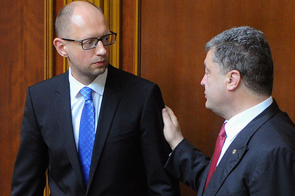 Ukraine's President Petro Poroshenko (R) talks to Prime Minister Arseny Yatseniuk during a parliament session in Kiev July 31, 2014. Ukrainian parliament rejected Prime Minister Arseny Yatseniuk's resignation on Thursday after approving legislation he said was needed to boost spending on the army and avoid a default. REUTERS/Andrew Kravchenko/Pool (UKRAINE - Tags: POLITICS CIVIL UNREST) - RTR40RKZ