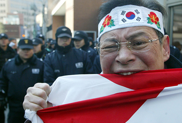Южнокорейский протестующий рвет зубами японский флаг