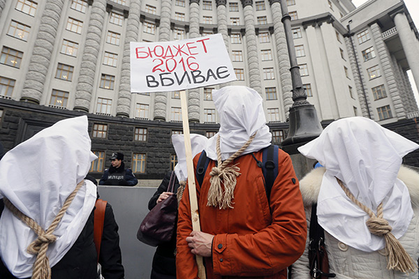 "Activists with bags on their heads and ropes around their necks demand an increase in state funding for the treatment of seriously ill people in front of the government building in Kiev, Ukraine, December 23, 2015. The placard reads, ""Budget 2016 kills."" REUTERS/Valentyn Ogirenko - RTX1ZVAV"