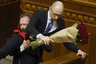 Rada deputy Oleg Barna removes Prime Minister Arseny Yatseniuk from the tribune, after presenting him a bouquet of roses, during the parliament session in Kiev, Ukraine, December 11, 2015. REUTERS/Valentyn Ogirenko      TPX IMAGES OF THE DAY      - RTX1Y7KB