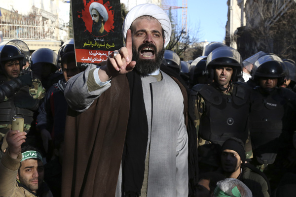 Surrounded by policemen, a Muslim cleric addresses a crowd during a demonstration to protest the execution of Saudi Shiite Sheikh Nimr al-Nimr, shown in the poster in background, in front of the Saudi embassy in Tehran, Iran, Sunday, Jan. 3, 2016