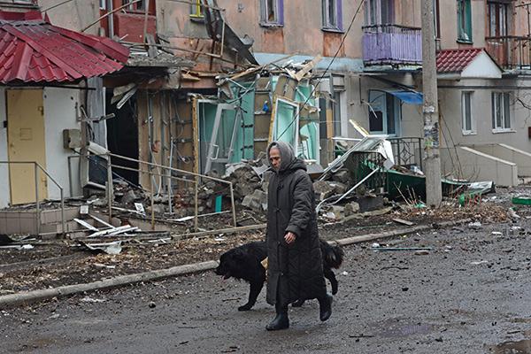 Жительница города Дебальцево идет с собакой мимо пострадавшего в результате обстрелов во время боевых действий жилого дома