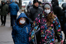 People wearing face masks walk in a street in Kiev, Ukraine, Thursday, Jan. 21 2016. The death toll from the flu outbreak in Ukraine has reached 60, a Health Ministry official said on Thursday. Earlier on Thursday, Kiev prolonged quarantine in schools and kindergartens over the flu and acute respiratory infection outbreak till January 27. (AP Photo/Sergei Chuzavkov)