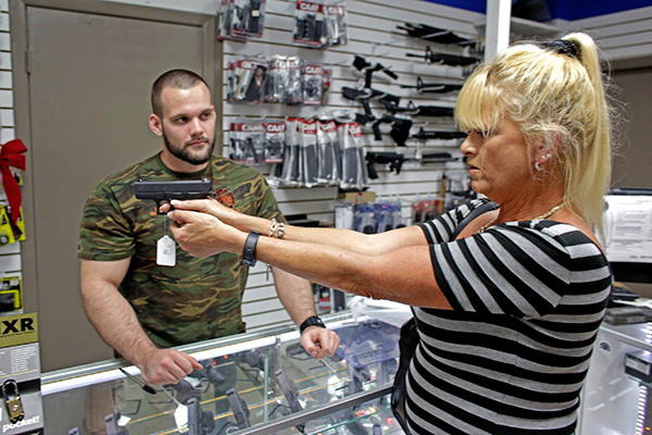 Sally Abrahamsen, of Pompano Beach, Fla., right, holds a Glock 42 handgun while shopping for a gun at the National Armory gun store and gun range, Tuesday, Jan. 5, 2016, in Pompano Beach, Fla. President Barack Obama unveiled his plan Tuesday to tighten control and enforcement of firearms in the U.S. At left is salesperson T.J. O'Reilly. (AP Photo/Lynne Sladky)