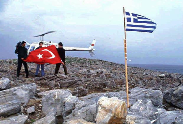 Турецкие журналисты поднимают турецкий флаг на острове Имиа