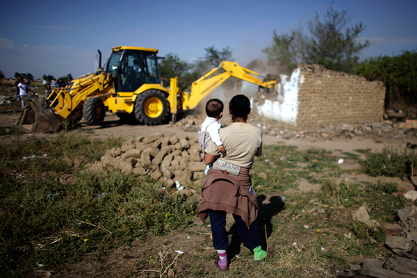 2012A Bulgarian Roma woman holds a child as they watch an excavator demolish a house in a Roma suburb in the town of Maglizh, some 260km (161miles) east of Sofia September 25, 2012. Municipal authorities started demolishing some 30 illegally built shacks and houses in the suburb on Tuesday. REUTERS/Stoyan Nenov