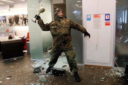 An ultra-right activist attacks an Alfa bank office in central Kiev, Ukraine, Saturday, Feb. 20, 2016.